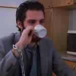 Um homem toma café com correntes no pulso