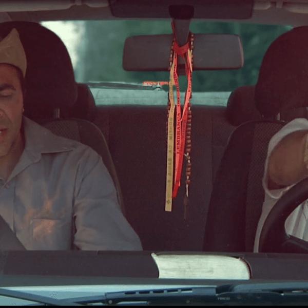 Dois homens em um carro conversando, um deles dirigindo e o outro segurando uma pá.
