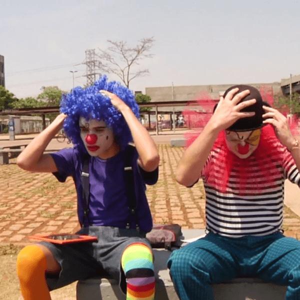 Dois palhaços com as mãos na cabeça e semblante preocupado sentados em uma praça