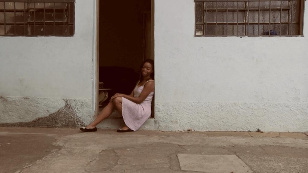 Jovem sentada na soleira da porta de uma casa