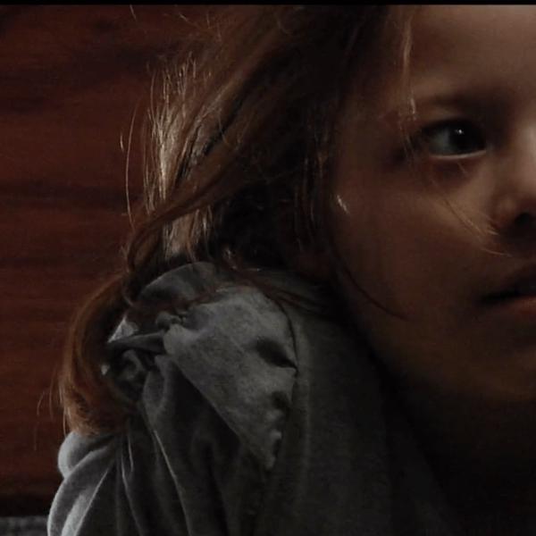 Uma menina de pijamas com olhar assustado