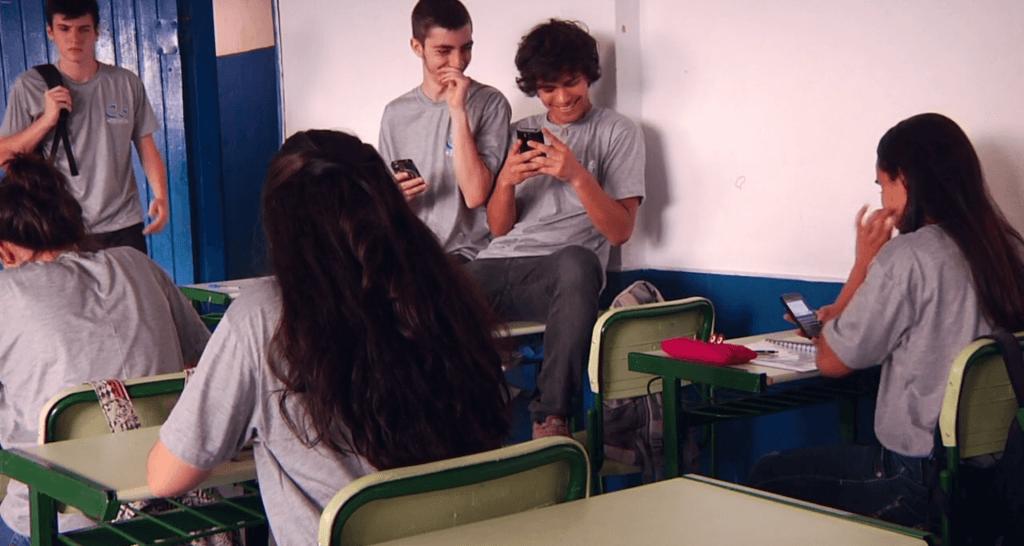 Adolescentes usando celular na sala de aula